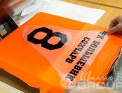 Оранжевые футболки с надписью «ФК БОЛЬШЕВИК»